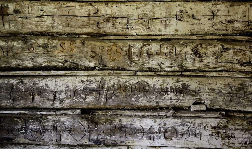 Interior wall of the Gibson House at Bannack State Park showing various cattle brands